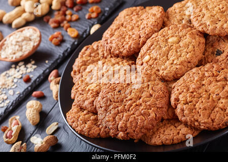 close-up of delicious Oatmeal raisin and peanut Cookies on a black plate with ingredients on a slate tray at the background, horizontal view from abov - Stock Photo