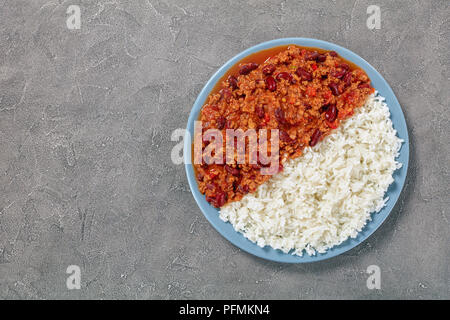 hot delicious chili con carne with whole red kidney beans on plate with boiled rice on concrete table, classic recipe, view from above - Stock Photo