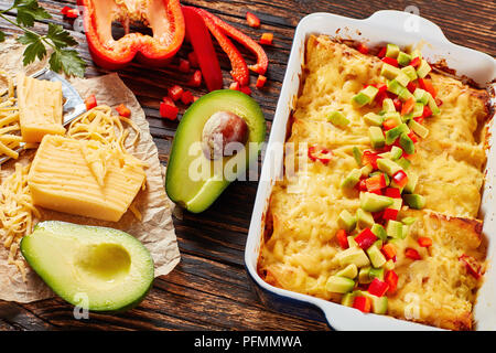 enchiladas of rolled corn tortillas stuffed with shredded meat, sauce, grated cheese and pieces of chili in baking dish sprinkled with avocado and bel - Stock Photo