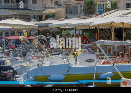boats and tavernas in the harbour at kassiopi on the greek island of corfu in greece - Stock Photo
