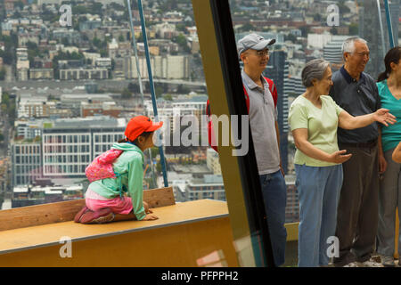 A girl curiously looks at  her family talking and laughing next to her at the top of Space Needle observation deck, Seattle, Washington, USA. - Stock Photo