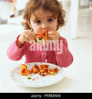 Baby girl sitting at table eating chicken enchiladas, enchilada pieces on plate in front of her, close-up - Stock Photo