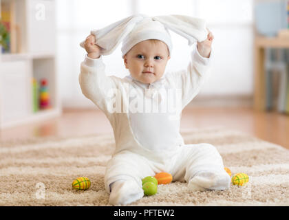 Funny baby girl in rabbit costume sitying on rug in nursery - Stock Photo