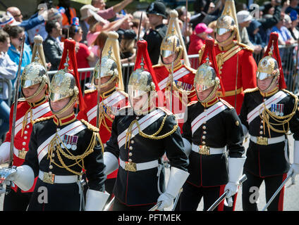 Members of the Household Cavalry Life Guards (red tunics) and Blues & Royals (blue tunics) march through Windsor before the Royal Wedding - Stock Photo