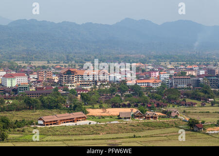 Hotels in downtown Vang Vieng viewed from above on a sunny day in Laos. - Stock Photo