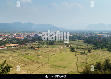 Beautiful view of town and fields from above in Vang Vieng, Vientiane Province, Laos, on a sunny day. - Stock Photo