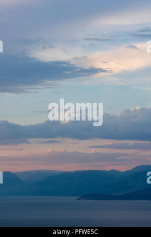 Sunset over the Albanian coast and mountains viewed from the hills above kassiopi on the greek island of corfu. - Stock Photo