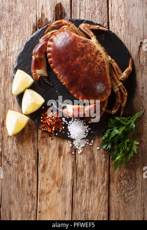 Raw brown crab with lemon, parsley and spices on a slate board close-up on a wooden table. Vertical top view from above - Stock Photo