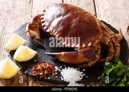 Raw fresh crab with herbs, lemon, salt and pepper closeup on the table. horizontal - Stock Photo