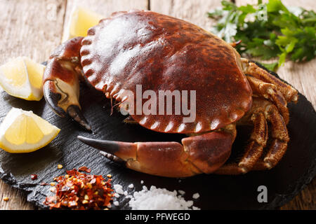 Raw brown crab with lemon, parsley and spices on a slate board close-up on a wooden table. horizontal - Stock Photo