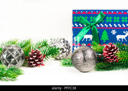 Fir branches on white decorated with christmas toys, gift box on white. Space for text. - Stock Photo