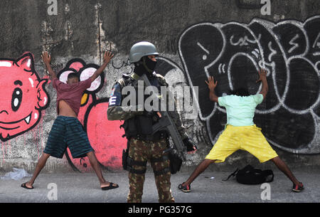 Rio de Janeiro, Brazil. 22nd Aug, 2018. A Brazilian soldier monitors suspects in the favela 'Alemão' during a raid against drug trafficking. Credit: Fabio Teixeira/dpa/Alamy Live News - Stock Photo