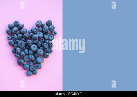 Delicious freshly picked bluberry in a form of heart on purple and pink background with copyspace. Healthy food concept. - Stock Photo