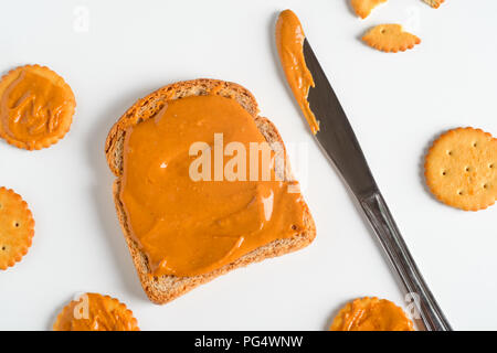 Whole wheat peanut butter sandwich, close-up. Knife, crackers, white background. - Stock Photo