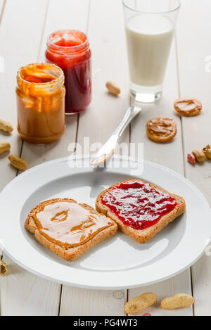 Delicious sandwich, glass of milk, jam and peanut butter jars, crackers. Light wooden background. - Stock Photo