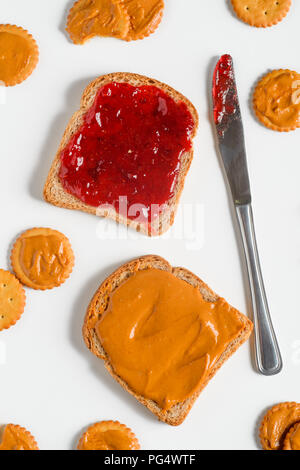 Delicious traditional jam and peanut butter sandwich, top-view. Knife, crackers, light background. - Stock Photo