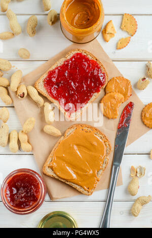 Yummy jelly and peanut butter jars, traditional sandwich and crackers, top-view. Baking paper, wooden background. Classic sweets. - Stock Photo
