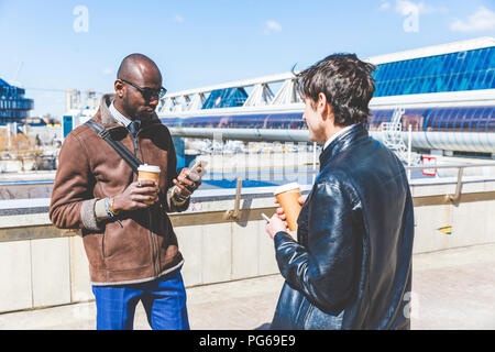 Russia, Moscow, two businessmen with coffee to go and smartphone in the city - Stock Photo