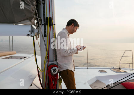 Marure man on catamaran, using smartphone - Stock Photo