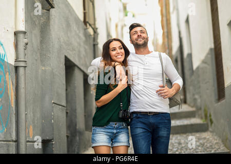 Happy tourist couple walking in the city - Stock Photo