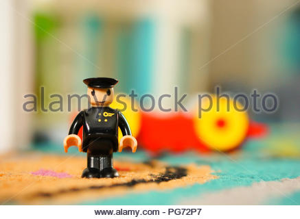 Plastic black toy pilot figure standing on a floor in soft focus - Stock Photo