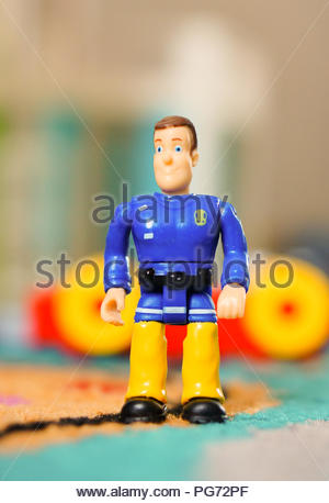 Fireman Sam toy figure standing on a floor in soft focus - Stock Photo