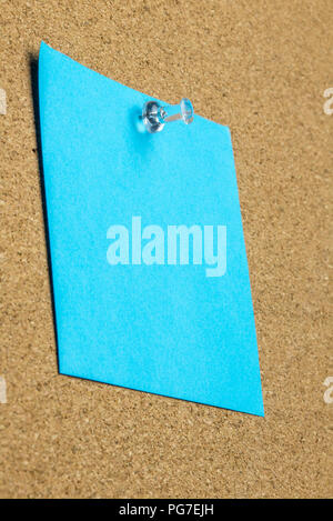 Blank sheet of blue paper with copyspace pinned up on a cork bulletin board with a thumb tack viewed at an oblique angle from below. - Stock Photo