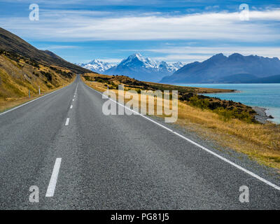 New Zealand, South Island, empty road with Aoraki Mount Cook and Lake Pukaki in the background - Stock Photo