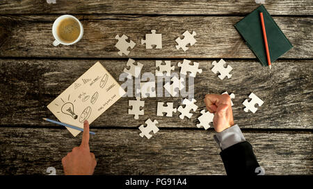 Top down view on thumb up and finger pointing to business symbols on notecard beside blank jigsaw puzzle pieces, checkbook and cup over old wooden tab - Stock Photo