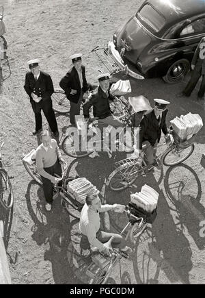 1950s mailmen. The post is ready to be delivered and the mailmen are sitting on their delivery bicycles with the letters and magazines in the rack in front. Sweden 1951   Photo Kristoffersson AO9-7 - Stock Photo