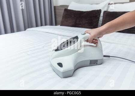 Mite vacuum cleaner using cleaning bed mattress dust eliminator with UV lamp - Stock Photo