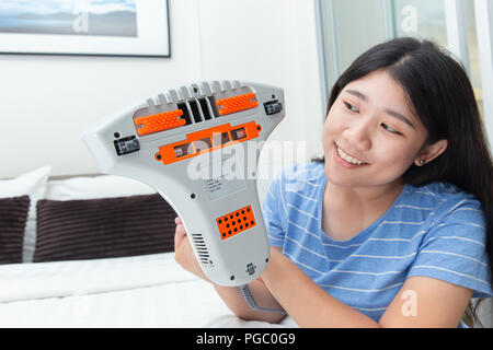 Girl enjoy using mite vacuum cleaner using cleaning bed mattress dust eliminator with UV lamp - Stock Photo