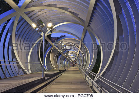 Puente de Arganzuela - modern footbridge steel structure illuminated at dusk in Madrid Spain Europe. Designed by French architect Dominique Perrault. - Stock Photo