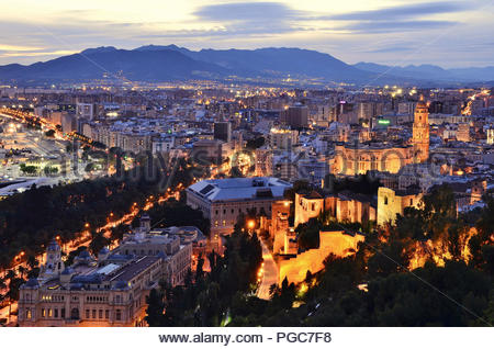 Alcazaba fortress and historic cathedral illuminated at dusk. City of Malaga viewed from Mount Gibralfaro in Andalusia Southern Spain Europe. - Stock Photo