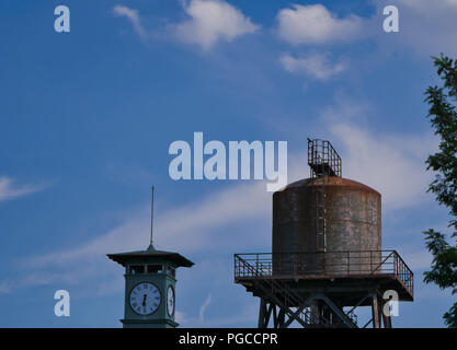 Very old partly rusty water tower with a clock tower in the foreground and blue sky in the background - Stock Photo