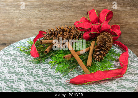 Three white pine cones on a bed of cedar and balsam branched, with six gold twig balls, three red ornaments, and five cinnamon sticks - Stock Photo