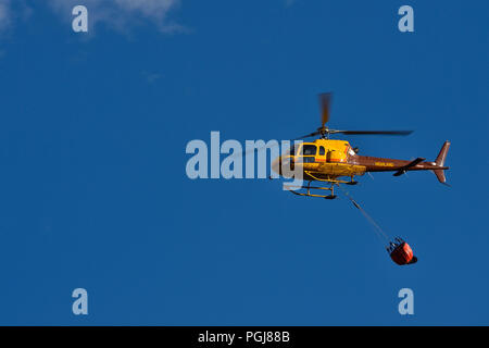 A horizontal image of a yellow helicopter carrying a bucket of water to a forest fire in rural Alberta Canada. - Stock Photo