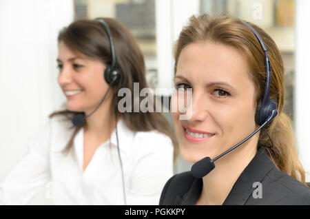Frendly female customer service during phone call at her desk - Stock Photo