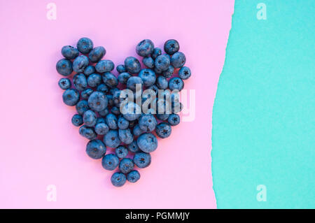 Delicious freshly picked bluberry in a form of heart on blue and pink background with copyspace. Healthy food concept. - Stock Photo