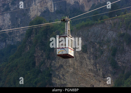 Cable car suspended over the Adige river near the church of St Apollinare and San Lorenzo bridge in Trento, Italy - Stock Photo