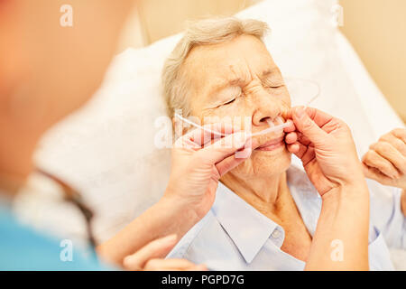 Senior as a patient with nasal cannula during an oxygen therapy in the hospital - Stock Photo