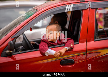 SIKKIM, INDIA - MAR 13, 2017: Unidentified Indian little boy looks out of the red car. - Stock Photo