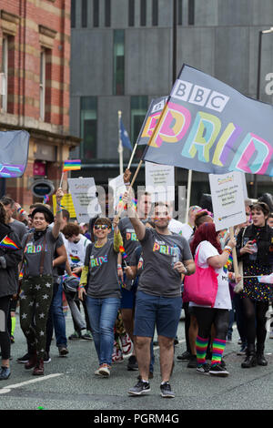 People wearing BBC Pride tee shirts carry a flag whilst taking part in the 2018 Manchester Pride Parade. - Stock Photo