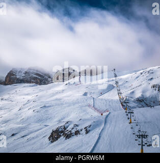 Ski lift goes up to the foggy top of the moutain. - Stock Photo