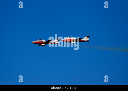 Two Canadian Snowbirds from Squadron 431 flying CT-114 Tudor jet airplanes do a fly-by at an air show over Nanaimo harbour on Vancouver Island British - Stock Photo