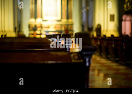 Wooden bench in the church on the colorfool background - Stock Photo