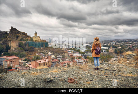 Woman in brown hat and backpack looking at Old medieval castle Narikala with overcast cloudy sky in Tbilisi, Georgia - Stock Photo
