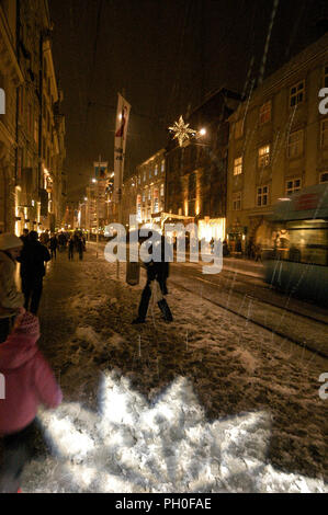 Late night shoppers shopping in a snow covered main shopping street with Christmas decorations and moving lights, lighting up the pavements in Herreng - Stock Photo