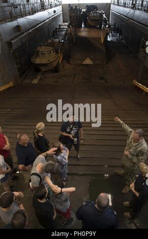 SEA (June 16, 2018) Engineman 1st Class Robert Petrach, from Vassar, Michigan, right, gives a tour of the Harpers Ferry-class dock landing ship USS Oak Hill (LSD 51) in Kiel, Germany, during Kiel Week 2018, June 16. Oak Hill, home-ported in Virginia Beach, Virginia, is conducting naval operations in the U.S. 6th Fleet area of operations. - Stock Photo