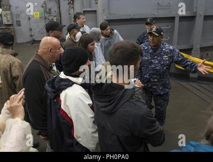 SEA (June 16, 2018) Cmdr. Rod Jacobo, executive officer of the Harpers Ferry-class dock landing ship USS Oak Hill (LSD 51), gives a tour of the ship in Kiel, Germany, during Kiel Week 2018, June 16. Oak Hill, home-ported in Virginia Beach, Virginia, is conducting naval operations in the U.S. 6th Fleet area of operations. - Stock Photo